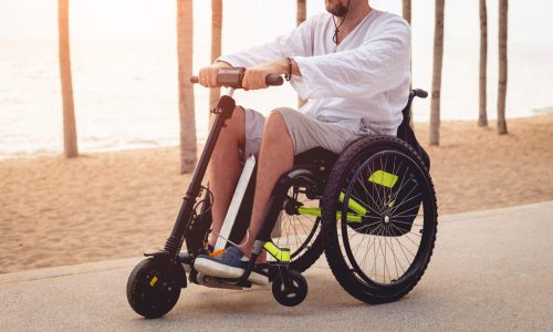 Disabled man in a wheelchair with electric scooter on the beach. Concept background