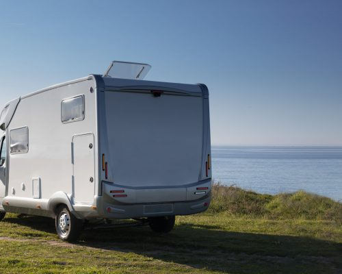 tourism-vacation-and-travel-camper-van-on-nature-over-sea-surface